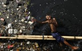 A boy plays in a polluted river after school at Pluit dam in Jakarta, Indonesia, June 5, 2009.