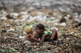 A girl plays with her brother as they search for usable items at junkyard near the Danyingone station in the suburbs of Yangon, Myanmar, in 2012.