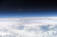 View of the crescent moon through the top of the earth's atmosphere. Photographed above 21.5°N, 113.3°E by International Space Station crew Expedition 13 over the South China Sea, just south of Macau (NASA image ID: ISS013-E-54329).